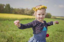 Little girl with outstretched arms standing on a meadow — Stock Photo