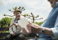 Due vecchi amici anziani che usano tablet digitali al parco — Foto stock