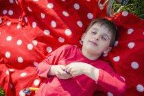 Garçon souriant avec les yeux fermés, allongé sur une couverture à pois rouge-blanc — Photo de stock