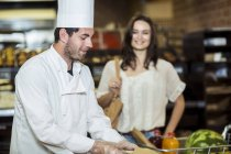Male chef in bakery helping female client in supermarket — Stock Photo