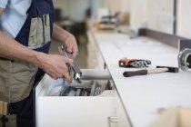 Handwerker hält Stück Metall — Stockfoto