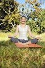 Усміхаючись жінка практикуючих йогу в луг — стокове фото