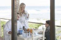 Família no pátio da casa de praia tomando café da manhã — Fotografia de Stock