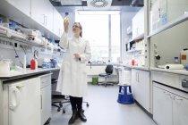 Jeune femme scientifique travaillant dans un laboratoire biologique inspectant des échantillons — Photo de stock