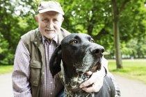 Portrait d'un homme senior avec son chien Braque allemand dans le parc de la ville — Photo de stock