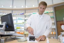 Young pharmacist stamping prescription — Stock Photo