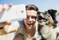 Jovem feliz tomando selfie com cão ao ar livre — Fotografia de Stock