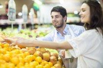 Ayudante de tienda ayudando a elegir naranjas del cliente - foto de stock
