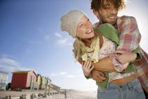 Happy young couple hugging on beach — Stock Photo