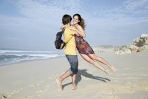 South Africa, man lifting up girlfriend on the beach — Stock Photo