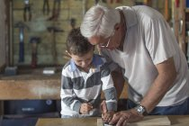 Grandfather and grandson working with wood in a garage — Stock Photo