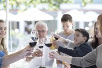 Extended family drinking red wine in restaurant — Stock Photo