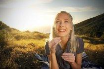Sorridente giovane donna in un paesaggio remoto guardando in alto — Foto stock