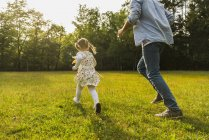 Father and daughter running with paper windmill on meadow — Stock Photo