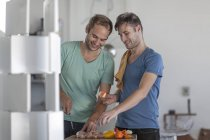 Happy gay couple preparing meat skewers in kitchen — Stock Photo