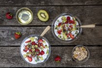 Bowls of Strawberry kiwi yogurt with cereals, chia seeds, agave syrup on dark wood — Stock Photo