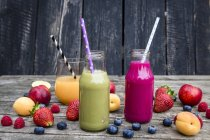 Different fruit smoothies in bottles and in glass with ingredients on wooden background — Stock Photo