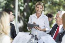 Serveuse qui prennent des clients commandes de déjeuner à table à l'aide d'une tablette numérique — Photo de stock
