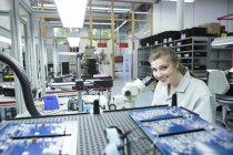 Portrait de technicien souriant examinant le circuit imprimé avec microscope — Photo de stock