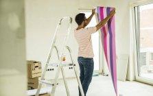 Young man renovating holding wallpaper — Stock Photo