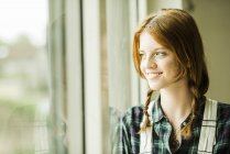 Sonriente a mujer joven mirando por la ventana - foto de stock