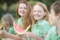 Kinder essen Scheiben Wassermelone im freien — Stockfoto