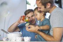 Гей пара печет торт с сыном — стоковое фото