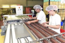 Two women working at production line in a baking factory — Stock Photo