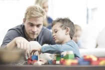 Padre e hijo pequeño jugando con juguetes de madera - foto de stock