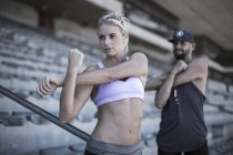 Portrait of sportswoman doing stretching exercies on grandstand of a stadium — Stock Photo