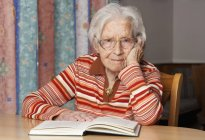 Portrait of senior woman with opened book — Stock Photo