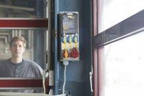 Tecnico in fabbrica dietro la porta di vetro — Foto stock