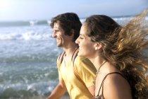Счастливая пара прогуливаясь вместе по пляжу — стоковое фото