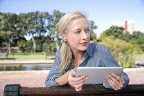 Young woman using digital tablet on park bench — Stock Photo