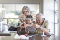 Дедушка и внук строят модель самолета под наблюдением бабушки — стоковое фото