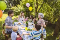 Family of three generations praying at a garden party — Stock Photo