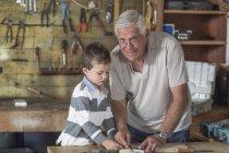 Дед и внук, работы с деревом в гараже — стоковое фото