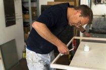 Rahmenbauer in der Werkstatt beim Bemalen eines Holzrahmens — Stockfoto