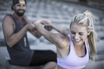 Sportswoman doing stretching exercises  on grandstand of a stadium with help from a friend — Stock Photo