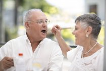 Wife feeding husband in outdoor cafe — Stock Photo