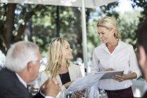 Garçonete pegando clientes pedidos de almoço na mesa, usando um tablet digital — Fotografia de Stock
