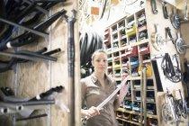 Giovane donna in un negozio di riparazione di biciclette con barra — Foto stock