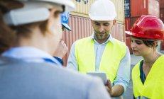 Quatre personnes avec casques de sécurité et de la tablette numérique parlant au port à conteneurs — Photo de stock