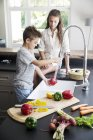 Brother and sister washing vegetables — Stock Photo