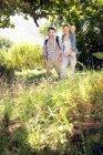 Couple souriant randonnée main dans la main dans le paysage rural — Photo de stock