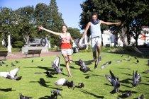 Pareja joven entusiasta persiguiendo palomas en el Parque - foto de stock