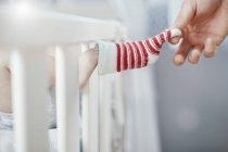 Vater ausziehen Baby Socke in Krippe — Stockfoto
