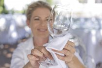 Waitress cleaning a wine glass with a cloth — Stock Photo