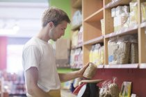 Male shop assistant in wholefood shop, weighing cereals — Stock Photo