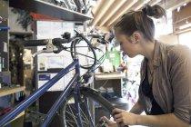 Jeune femme travaillant dans un atelier de réparation de vélo — Photo de stock